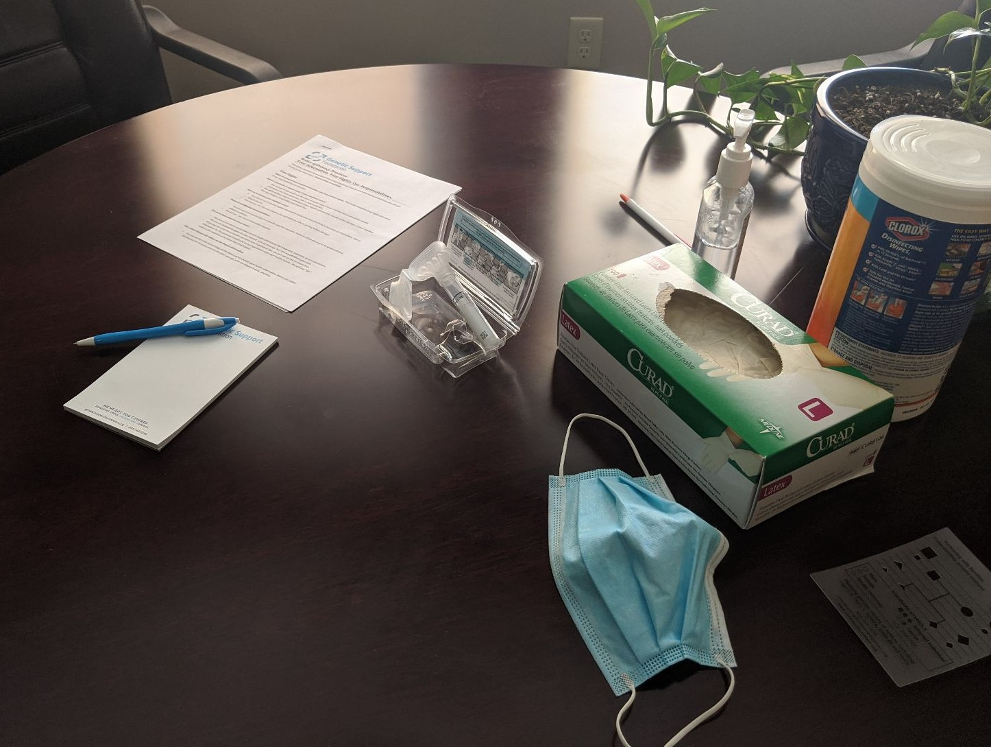 A mask, gloves, and sanitizer sit on a table for gentic testing and genetic counseling during Covid-19.