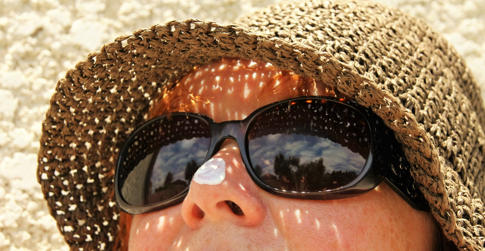 person wears hat, sunglasses, and sunscreen for protection against skin cancer
